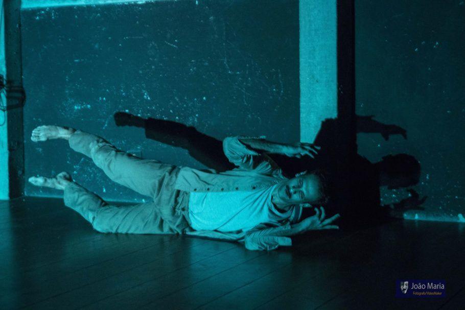 Bailarino deitado no palco com uma luz azul