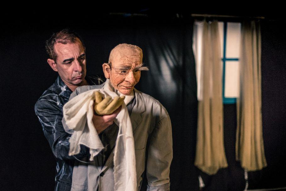 Um ator e um boneco ancião em cena