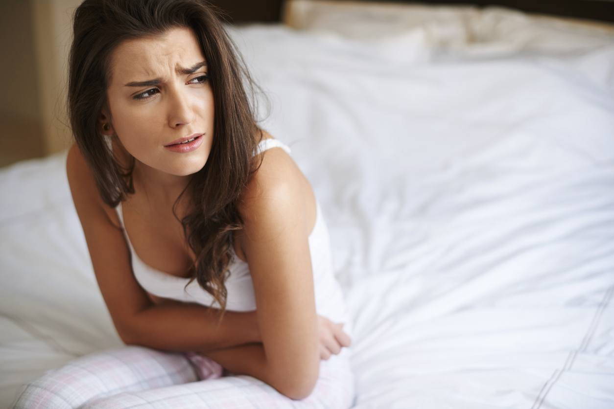 mulher na cama com cara de dor