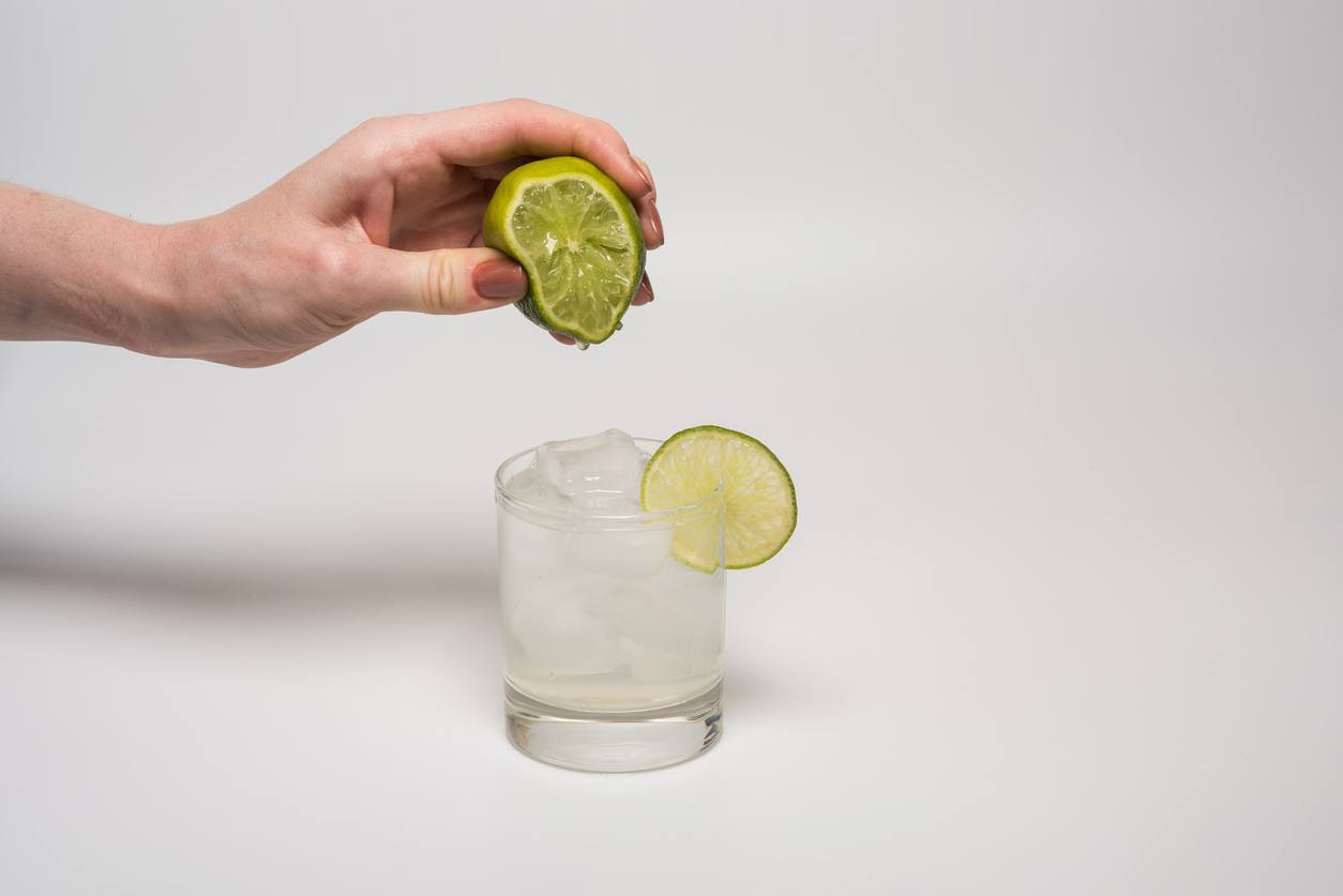 mulher espremendo limão em um copo d'água