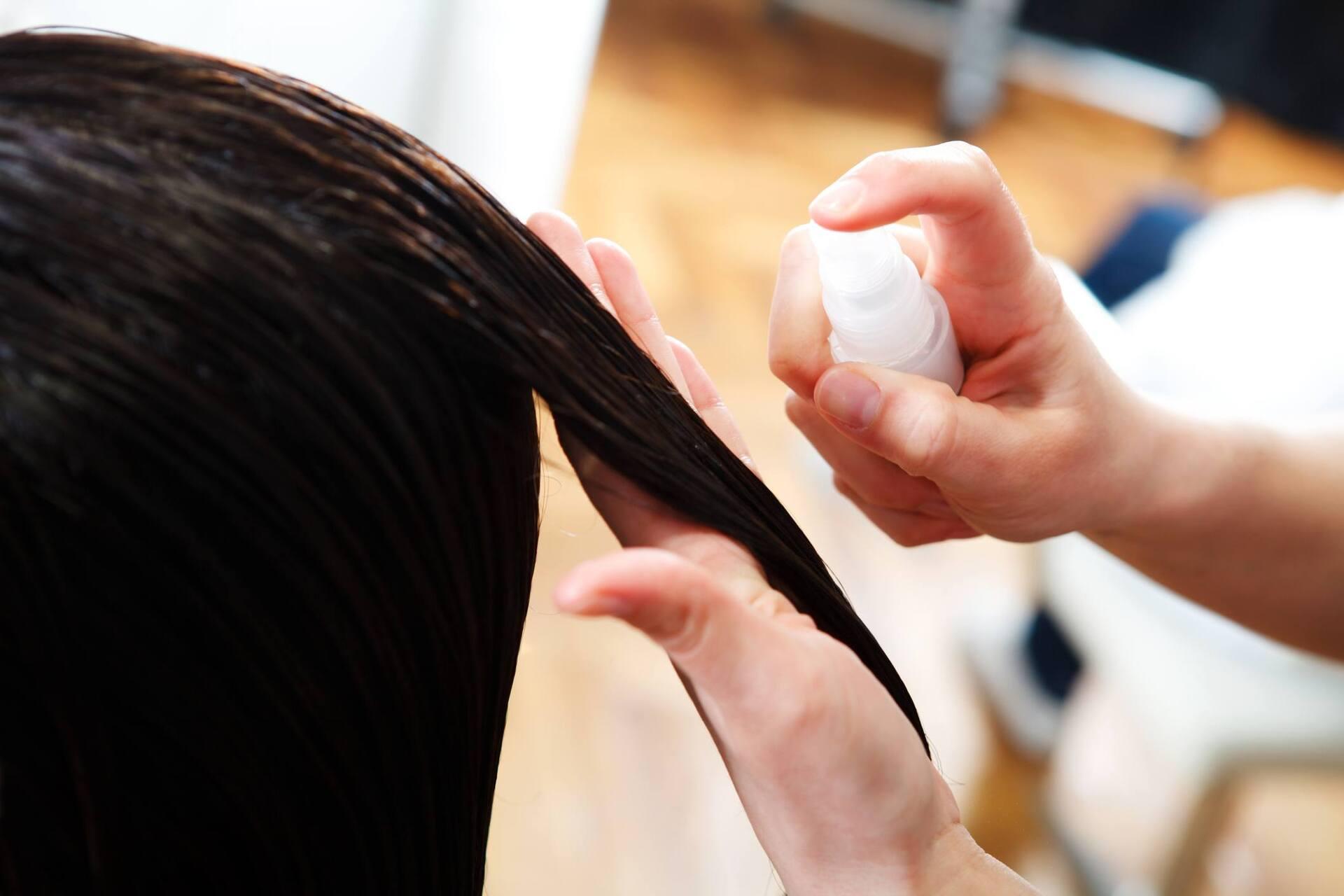 Mulher usando leave-in para dar mais volume ao cabelo