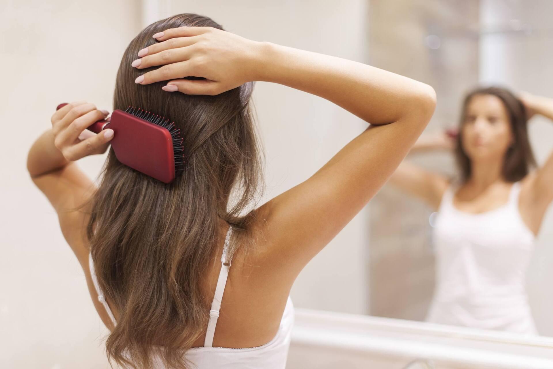 Mulher penteando os fios para dar mais volume ao cabelo