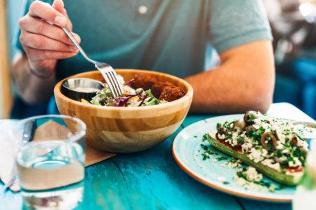 homem comendo comida a base de uma dieta vegana