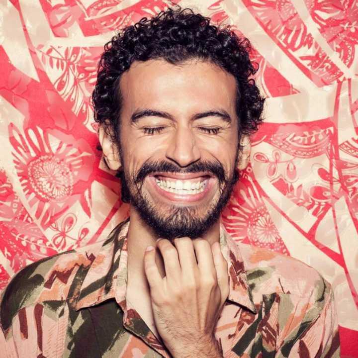 Foto em close do cantor Felipe Cprdeiro de olhos fechados segurando a gola da camisa