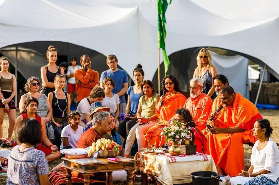 pessoas reunidas em torno de uma mesa no festival de yoga