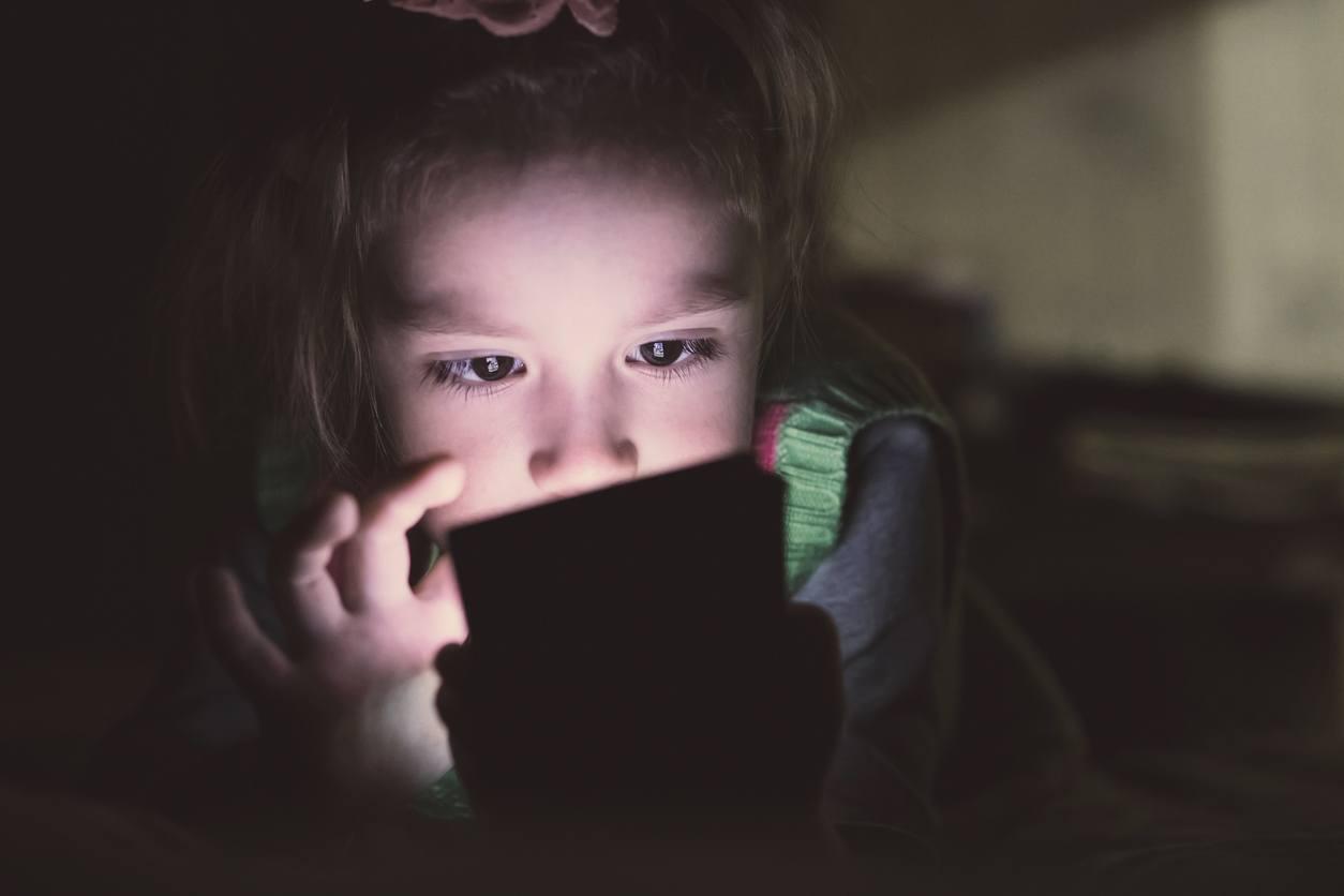 criança mexendo no celular deitada na cama