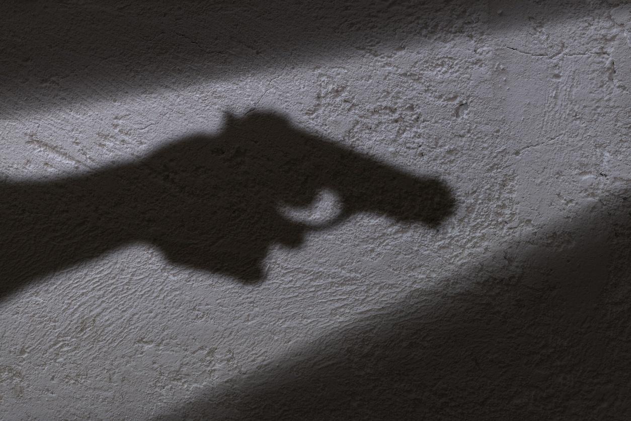 sombra de uma mão segurando uma arma de fogo
