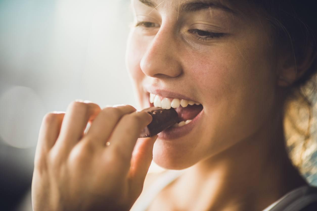 mulher comendo um pedaço de chocolate