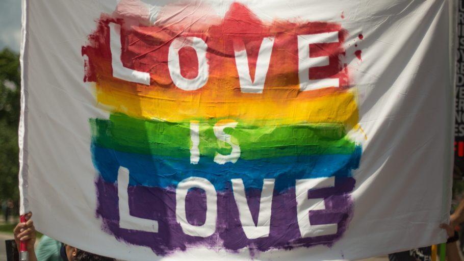Bandeira com os dizeres Love is Love nas cores da bandeira LGBT
