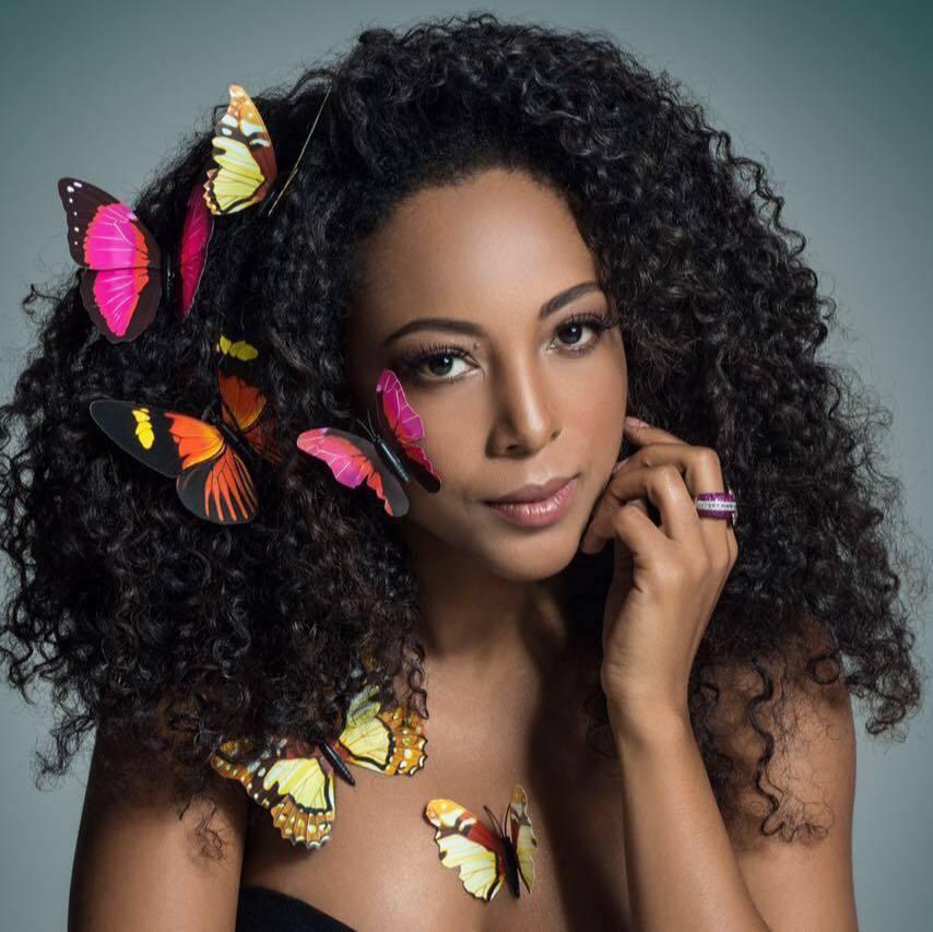 Foto em close da Negra Li com várias borboletas no cabelo