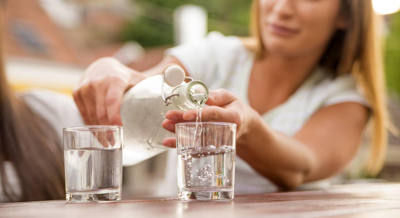 mulher colocando água no copo