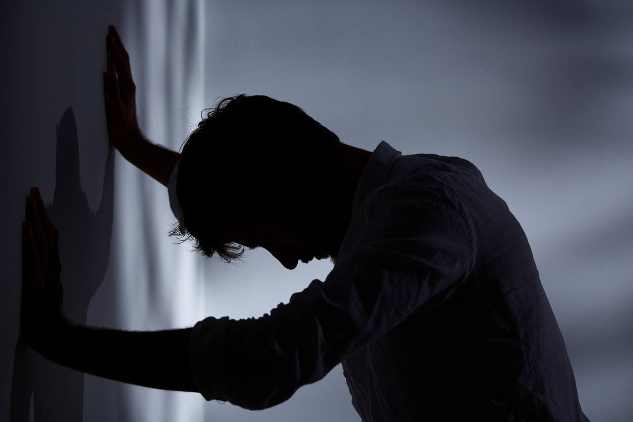 sombra de um homem com as mãos encostadas na parede