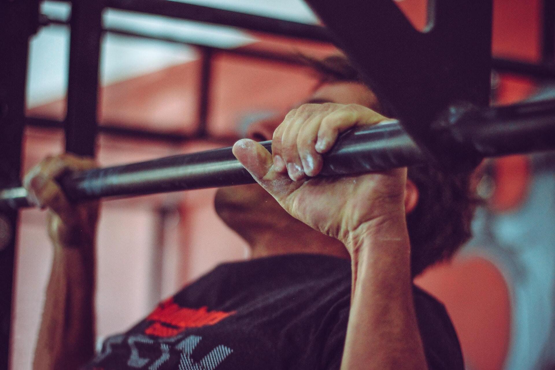 homem fazendo exercício na barra fixa