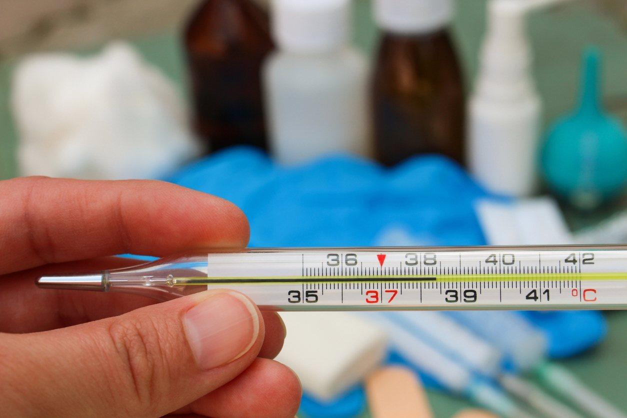 uma mão segurando um termômetro