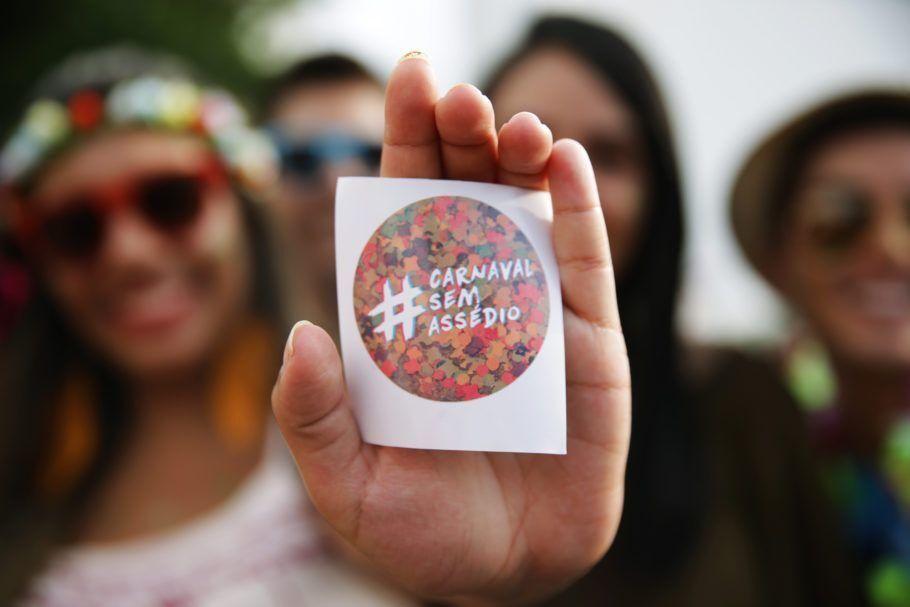 Foliã mostra adesivo da campanha contra assédio no Carnaval promovida pelo Catraca Livre