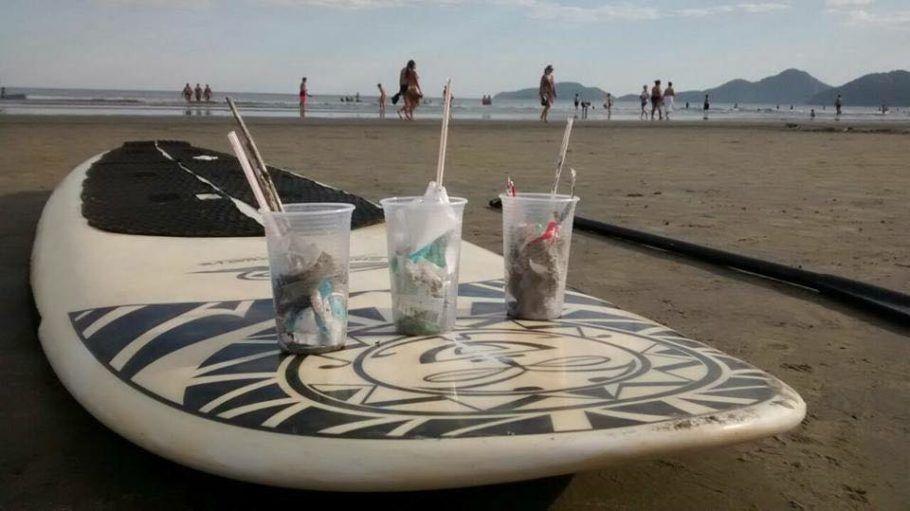 A coleta de lixo da praia serve de pagamento para aulas de stand up paddle