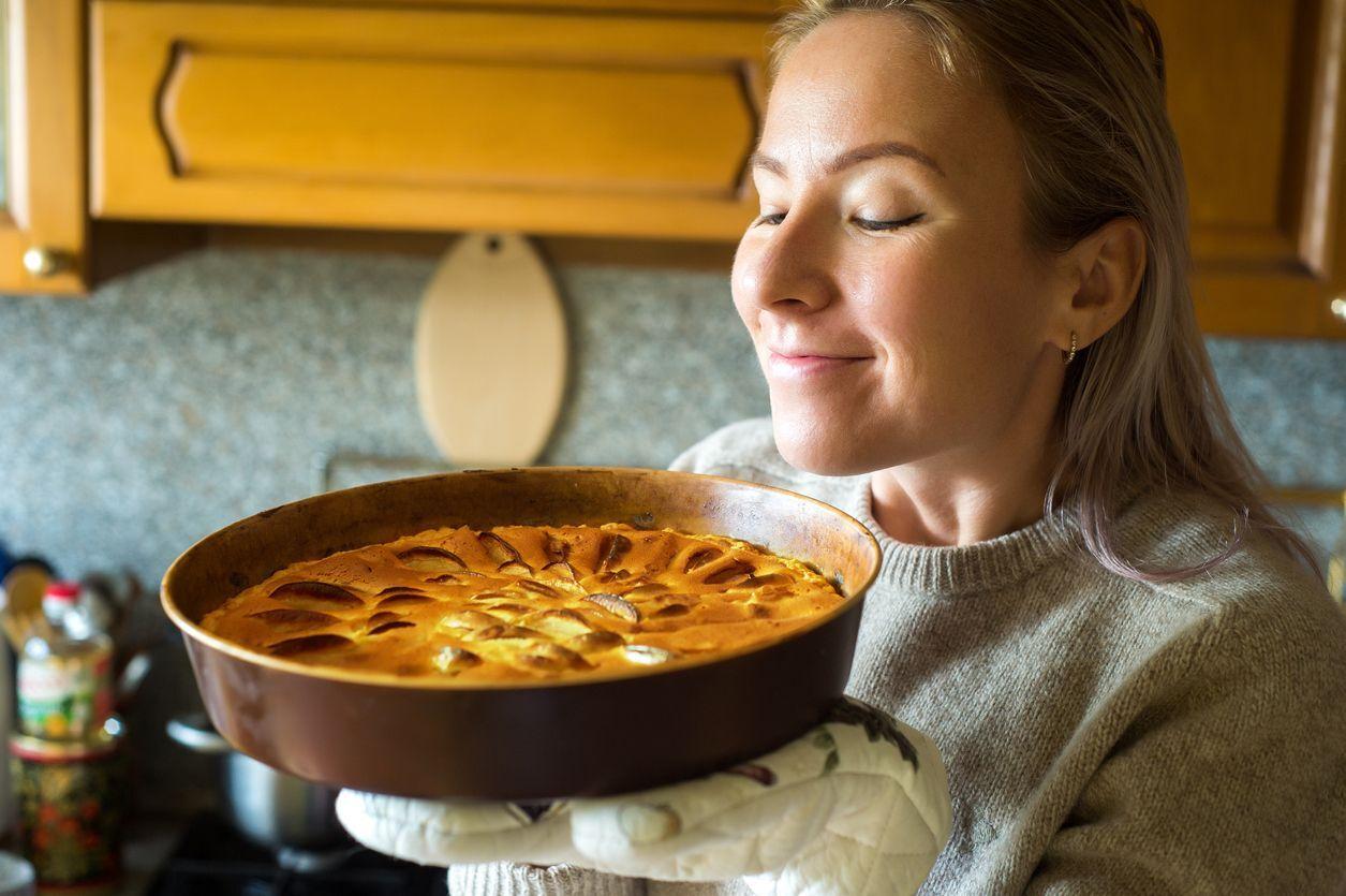 mulher cheirando uma torta