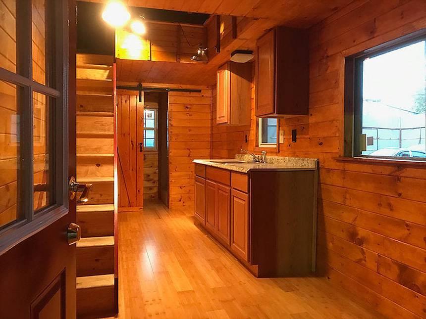 O primeiro andar da minicasa retrátil tem sala, cozinha e banheiro
