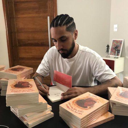 rapper rashid autografa seu livro ideias que rimam mais que palavras