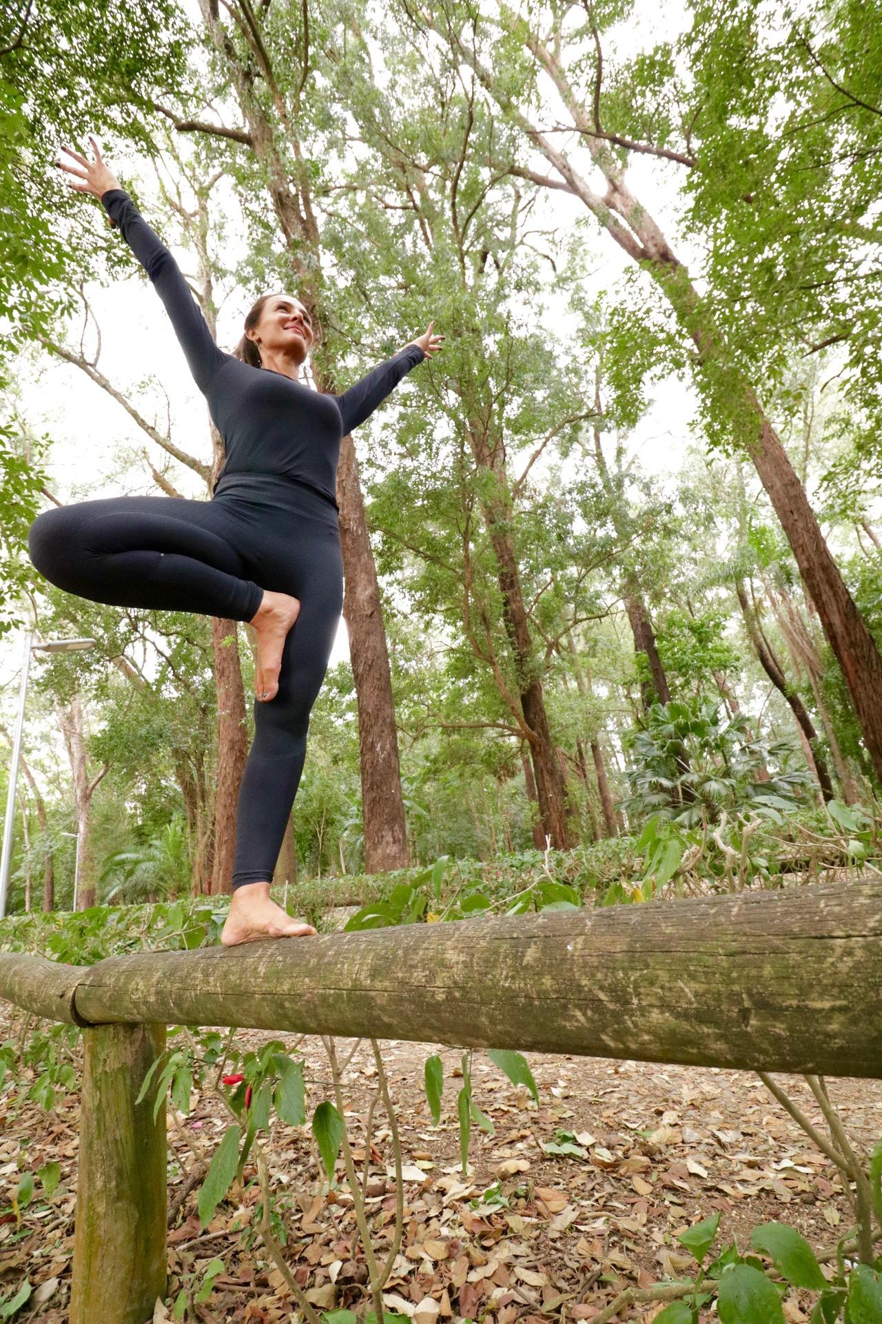 mulher se equilibrando em cima de um galho de árvore