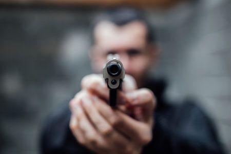 homem com arma de fogo