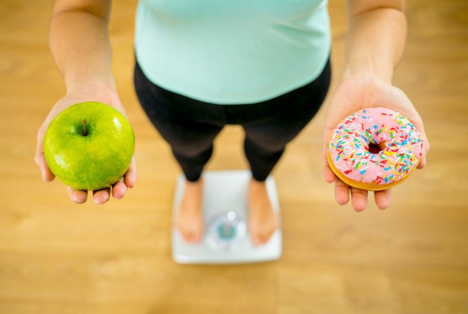 mulher na balança com um doce e uma maçã