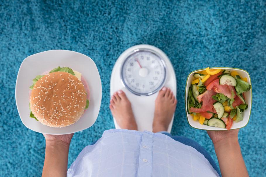 homem na balança segurando um hamburguer e um prato de comida