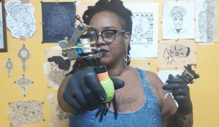 mulher tatuadora apontando a agulha de tatuagem