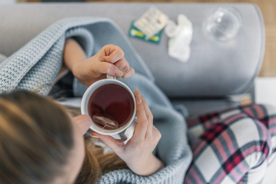 mulher doente tomando um chá no sofá