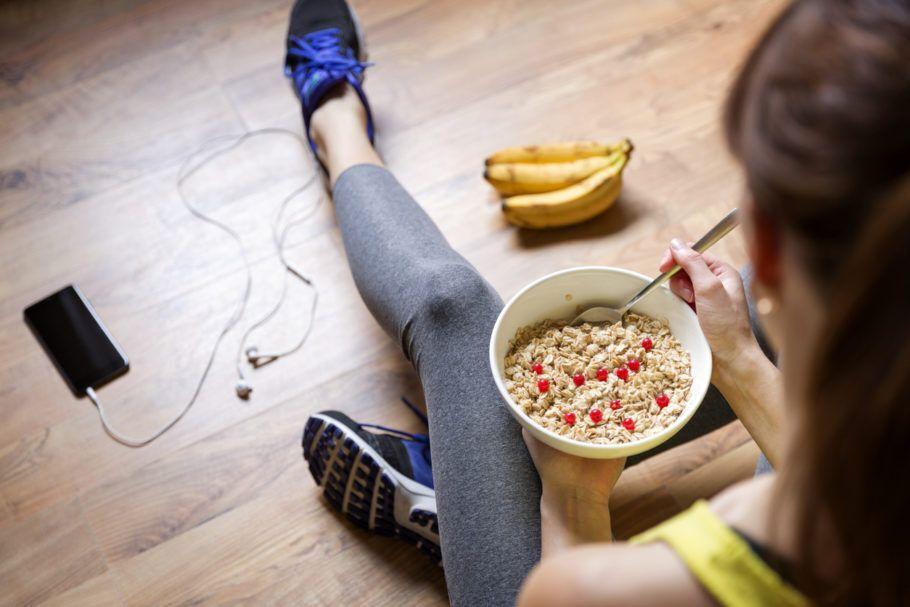 mulher com roupa de academia e comendo cereais e banana