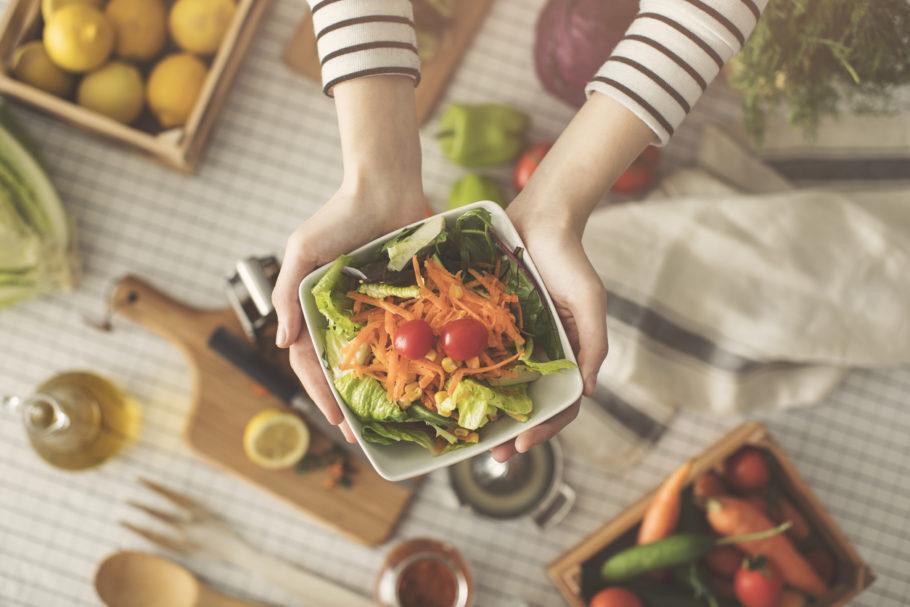 mulher segurando um pote de salada sobre uma mesa com frutas e legumes