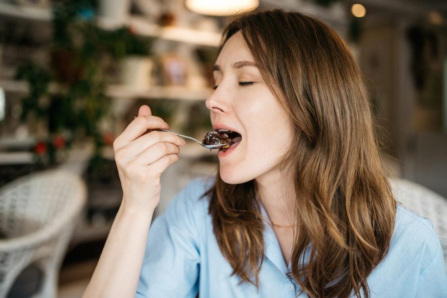 mulher comendo uma colher de doce de olhos fechados