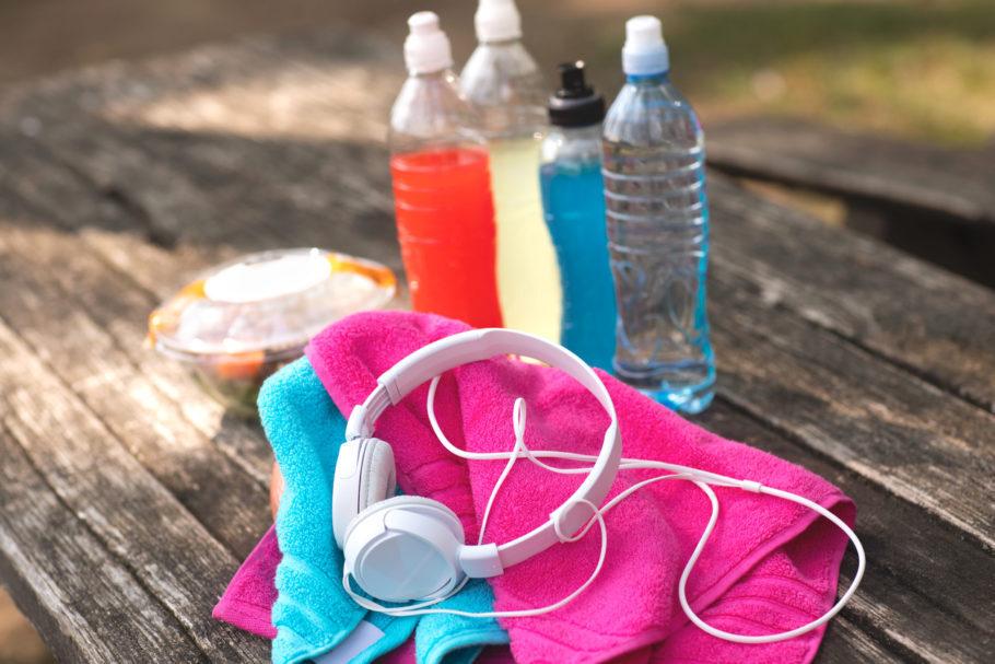 quatro garrafas com água e isotônicos perto de uma toalha e fone de ouviso