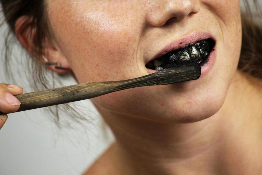 menina escovando o dente com pasta preta