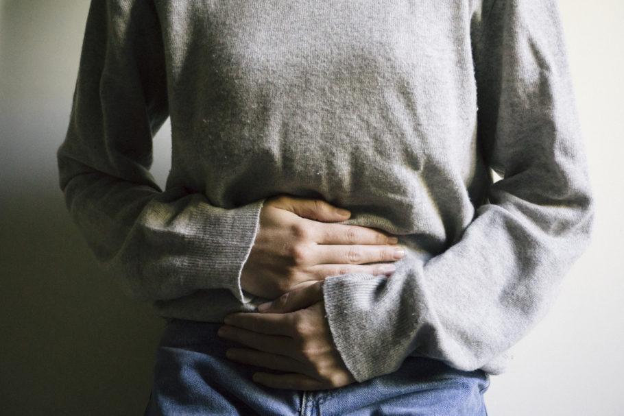mulher com as mãos na altura do estômago