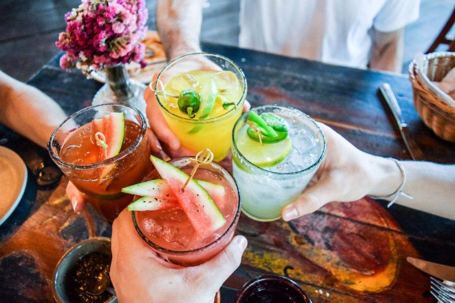 brinde com quatro pessoas segurando um drink diferente