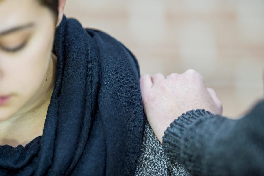 mulher sentada com a cabeça baixa e com alguém com a mão em seu ombro