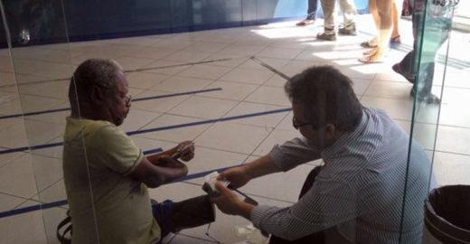 Funcionário de banco se senta no chão para atender cliente