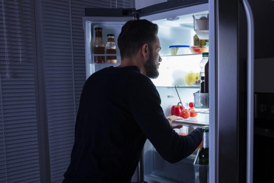 homem abrindo a geladeira à noite