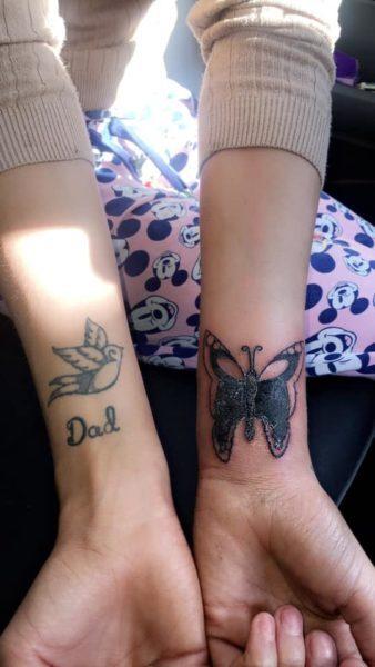 mulher com os dois braços estendidos mostrando duas tattoos, uma em cada pulso