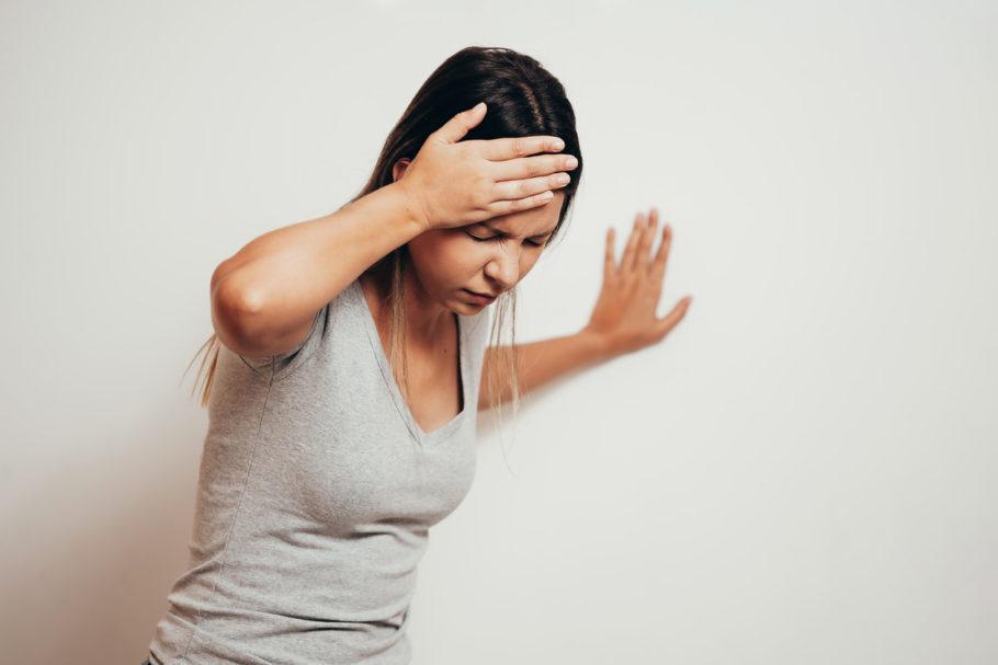 mulher com tontura se apoiando na parede