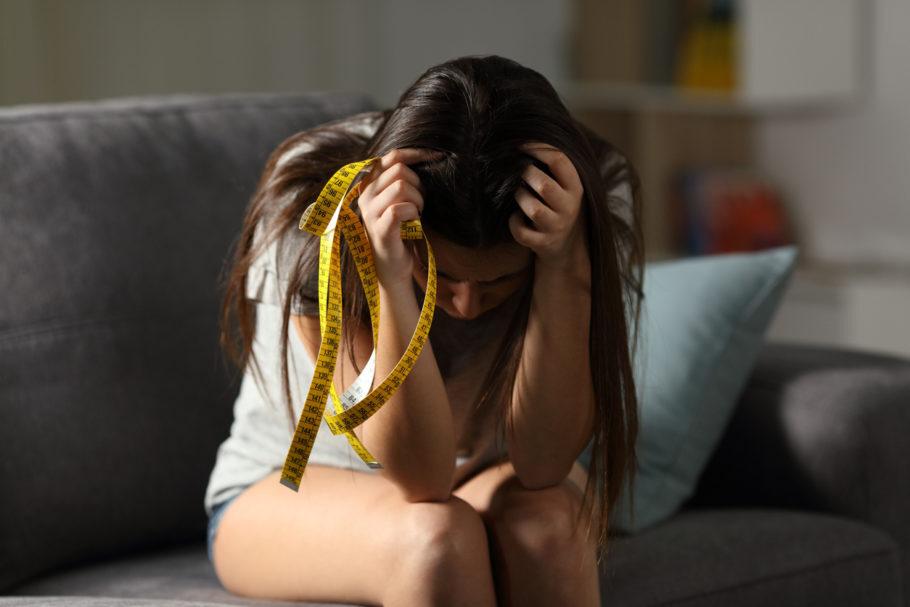 mulher sentada no sofá segurando uma fita métrica com as mãos na cabeça
