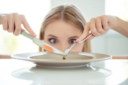 mulher comendo uma ervilha com o prato vazio