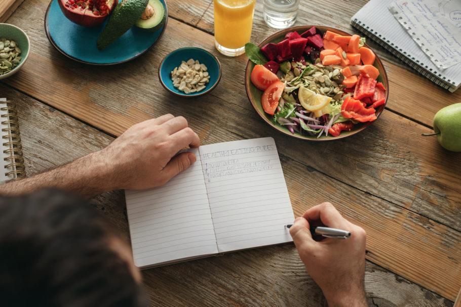 homem fazendo anotação em um caderno pero de um prato de comida