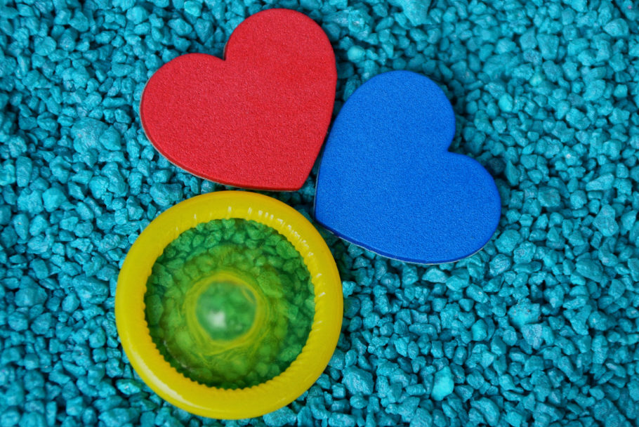 red and blue heart and yellow condom on small blue stones