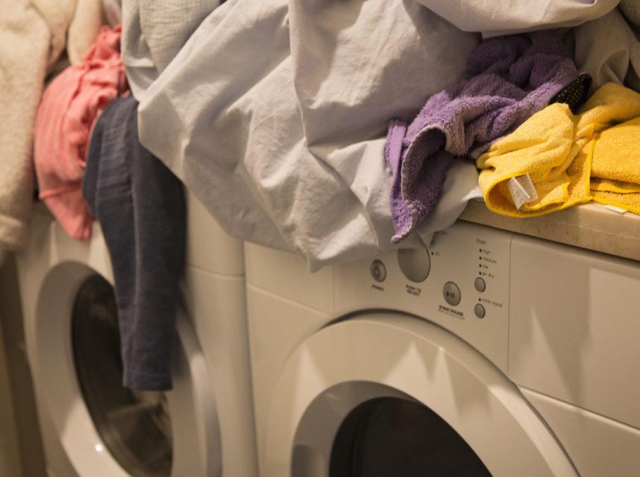 roupa de cama em cima da máquina de lavar
