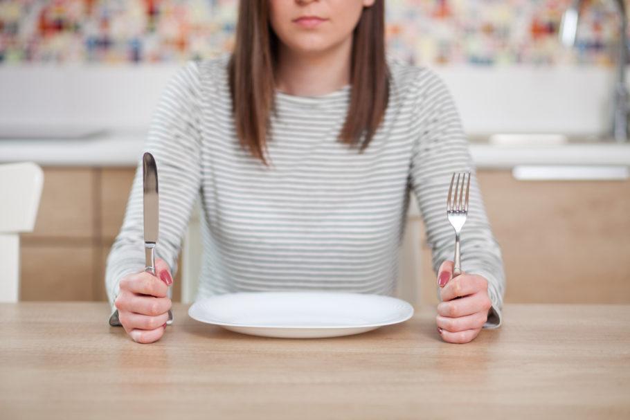 mulher com talher em frente a um prato vazio