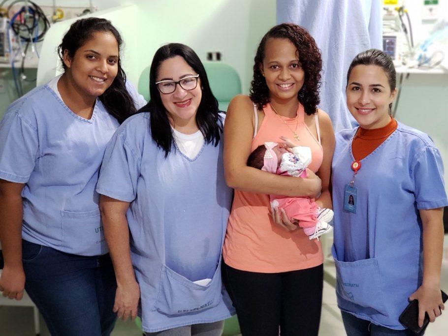 bebê no colo da mãe com as enfermeiras ao lado