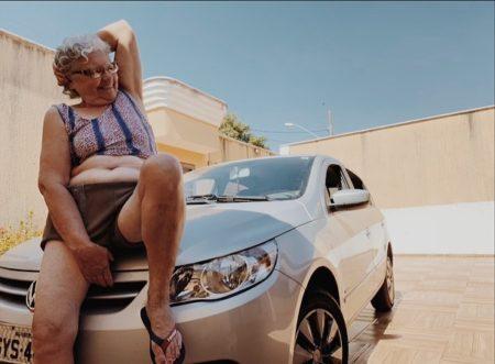 dona dirce sentada no capô do carro