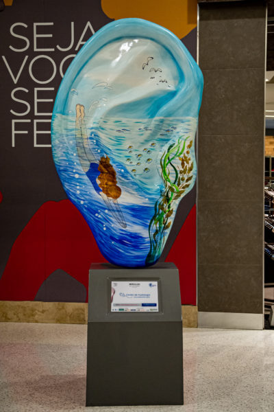 escultura de orelha gigante pintada como se fosse o fundo do mar